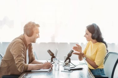 Two smiling radio hosts talking while recording podcast in broadcasting studio stock vector