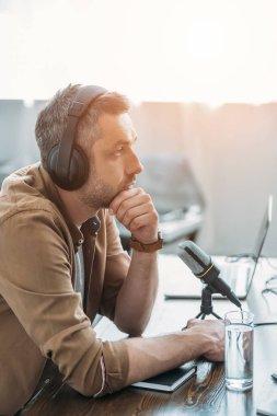Handsome serious radio host in headphones sitting near microphone in broadcasting studio stock vector