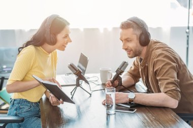 attractive radio host showing notebook to smiling colleague while sitting at workplace together