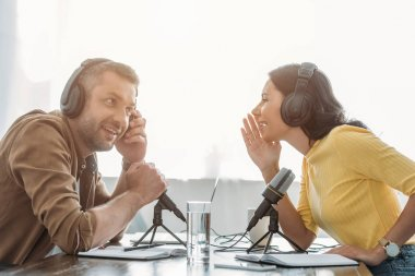 two cheerful radio hosts talking while recording podcast in radio studio