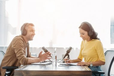Two smiling radio hosts in headphones talking while sitting at table in studio stock vector