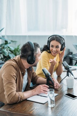 pretty radio host smiling and gesturing while recording podcast with colleague