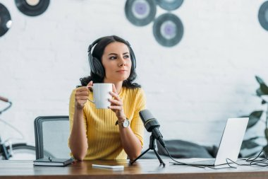 pensive radio host looking away while sitting at workplace and holding coffee cup