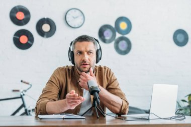 thoughtful radio host in headphones recording podcast in broadcasting studio