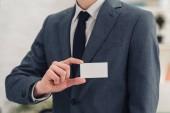 részleges kilátás üzletember mutatja be a kamera fehér üres névjegykártyát