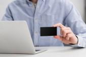levágott kilátás üzletember tartja üres fekete névjegykártya ülve munkahelyen