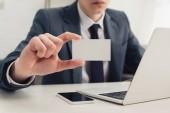 Fényképek részleges kilátás üzletember mutatja üres névjegykártyát a kamera ülve a munkahelyen