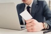 Fényképek részleges kilátás üzletember gazdaság üres névjegykártyát használata közben laptop