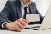 Fényképek részleges kilátás üzletember mutatja üres névjegykártyát a kamera használata közben laptop