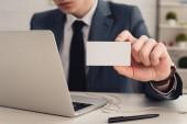 részleges kilátás üzletember gazdaság fehér névjegykártyát használata közben laptop