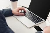 Teilansicht von Geschäftsmann mit Laptop in der Nähe von Coffee to go und schwarzer leerer Visitenkarte