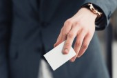 cropped view of businessman holding white empty business card