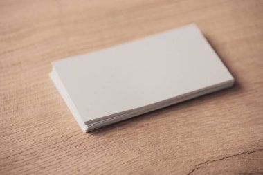 White empty business cards stacked on wooden textured surface stock vector
