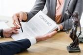 Ausgeschnittene Sicht von Geschäftsleuten mit Vertrag in der Hand