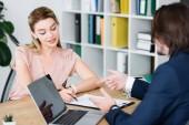 okouzlující žena, která sedí v kanceláři s obchodníkem a podpisem smlouvy