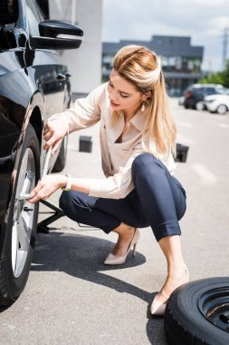businesswoman fixing wheel on broken auto, car insurance concept
