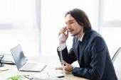 obchodník Mluvil po telefonu, seděl v kanceláři a odvrátil pohled