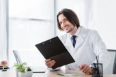 happy doctor with clipboard in hand looking at camera while sitting in office