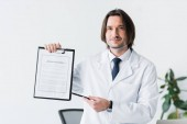 smiling doctor in white coat looking at camera and pointing with pen at medical document