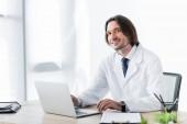 šťastný doktor v bílém kabátě při práci s laptopem