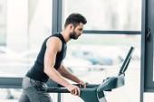 Hübscher Sportler läuft auf Laufband im Sportzentrum