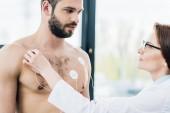 Fotografia medico mettendo elettrodi su sportivo senza camicia durante il test di resistenza