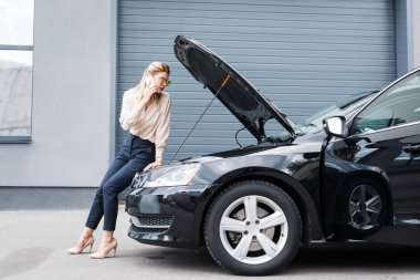 businesswoman talking on smartphone while standing near broken auto, car insurance concept