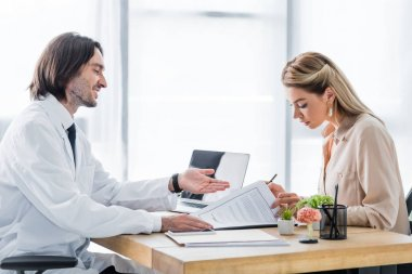 woman signing insurance claim form during appointment with doctor in clinic