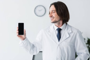 Happy doctor in white coat holding smartphone in hand and looking at display with copy space stock vector