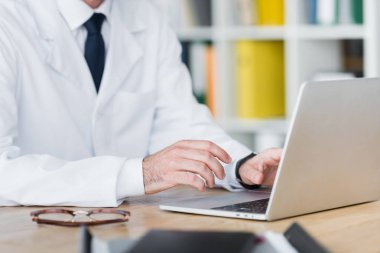 Cropped view of doctor in white coat working with laptop stock vector