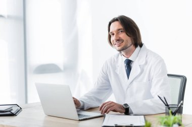 Happy doctor in white coat looking at camera while working with laptop stock vector