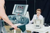 Fényképek orvos a kitartást vizsgáló pultnál a sportolóval a tornateremben