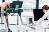 Fényképek orvos nézi a monitort, míg végző kitartást vizsgálatot sportember a tornateremben