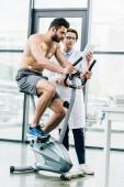 bel medico con tablet digitale vicino sportivo senza camicia durante il test di resistenza