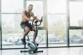 Fotografie lächelnder hübscher Sportler mit Elektroden auf Ellipsentrainer während Ausdauertest im Fitnessstudio