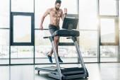 hübscher Sportler mit Elektroden läuft auf Laufband während Ausdauertest im Fitnessstudio