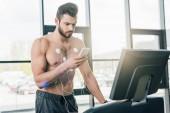 Sportler mit Smartphone läuft auf Laufband beim Ausdauertest im Fitnessstudio