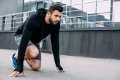 szép sportember kiindulási helyzetben kész futni