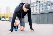 sportovec v mikina ve výchozí pozici připravený ke spuštění