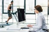 Arzt nutzt Computer, während Sportler beim Ausdauertest im Fitnessstudio auf Laufband laufen