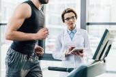 Fényképek sportoló fut a futópad közelében orvos digitális Tablet során tartóssági vizsgálat tornaterem