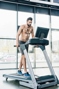 handsome muscular sportsman with electrodes running on treadmill during endurance test in gym