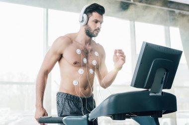muscular sportsman in headphones running on treadmill during endurance test in sports center