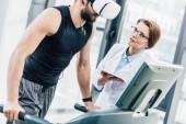 sportivo in vr auricolare allenamento sul tapis roulant vicino medico durante il test di resistenza in palestra