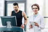 Fényképek sportember futó futópad közelében vonzó orvos kitartást vizsgálat edzőteremben