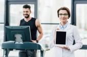 Fényképek sportoló fut a futópad közelében orvos bemutató digitális Tablet alatt tartóssági vizsgálat tornaterem