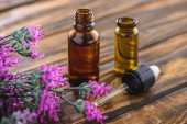 Photo bottles with essential oils, dropper and heather plant on wooden surface