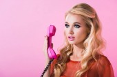 Fotografie beautiful girl posing with retro telephone isolated on pink, doll concept