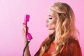 beautiful girl pouting lips and posing with retro telephone isolated on pink, doll concept