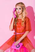 beautiful girl talking on retro telephone on pink, doll concept